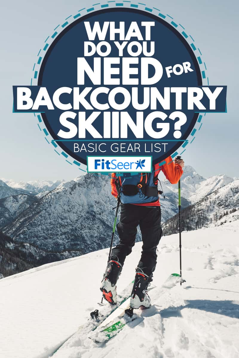 A well geared skier hiking on a snow trail, What Do You Need for Backcountry Skiing? [Basic Gear List]
