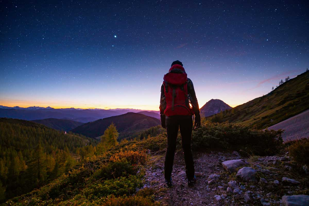 rear view woman hiker solo traveller with backpack standing alone in the mountains after sunset and blue hour watching starry sky