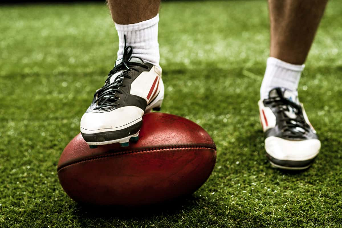 A football player putting his football cleats on a ball on the grass field, 3 Types Of Football Cleats You Should Know