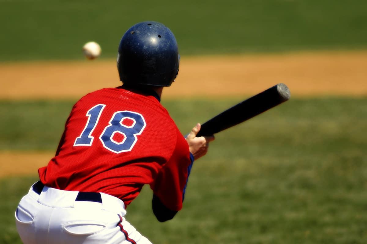 A baseball batter swinging the bat to hit the ball