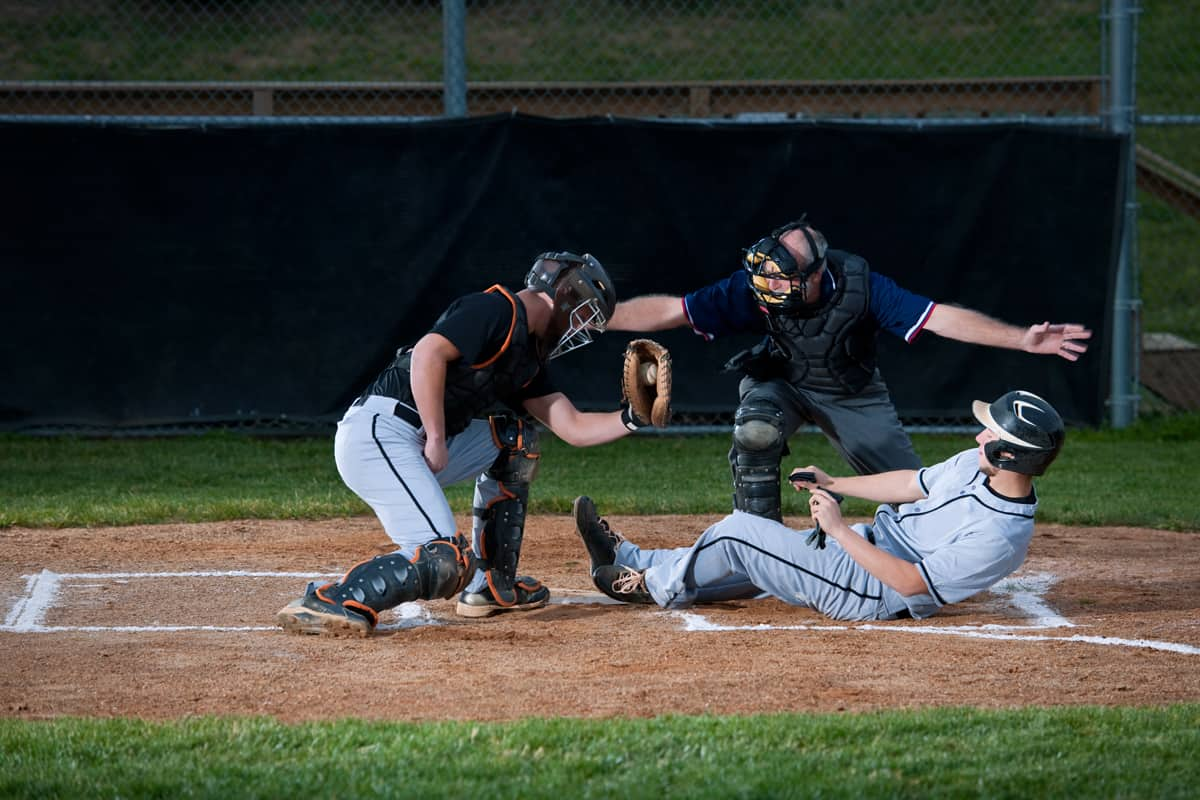 A baseball player making a score by sliding to an infield as the umpire guards the plate