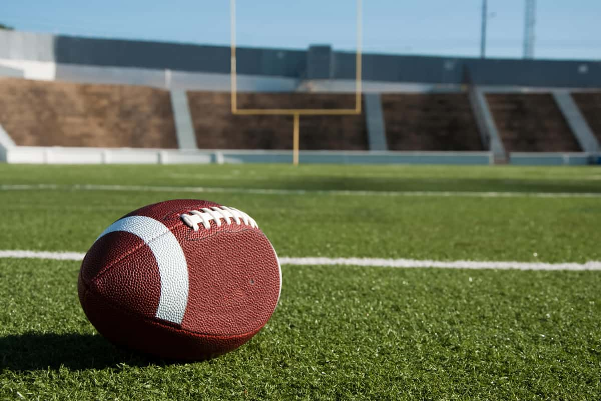 A football on a grass field with the goal post and bleachers on the background