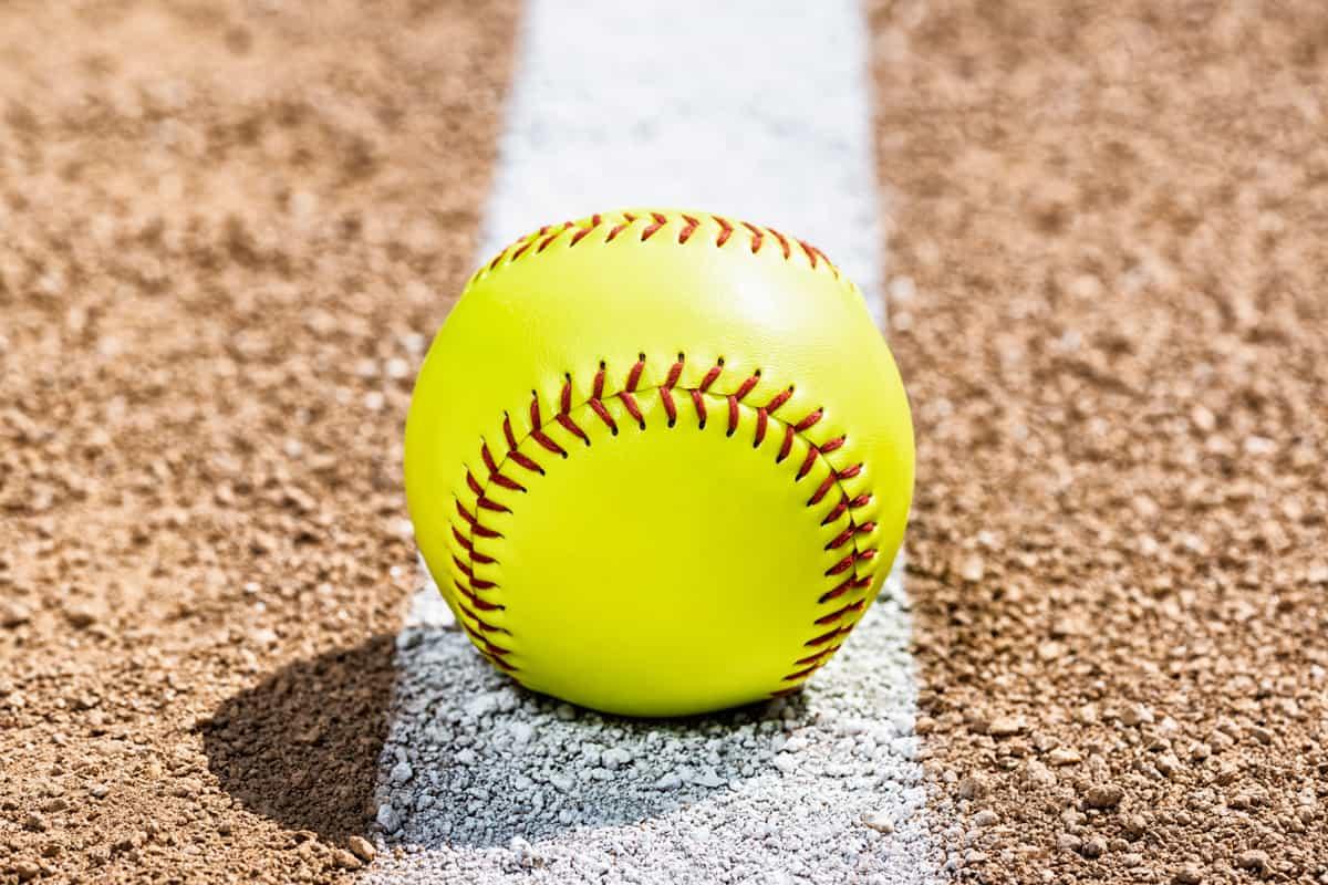 A softball placed on a foul line of a baseball field