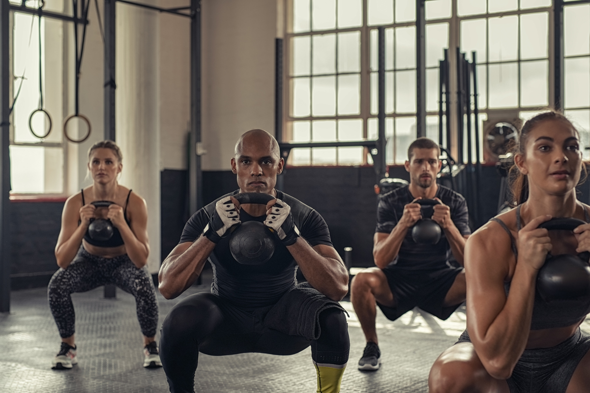 A team of Athletes working out using kettlebells