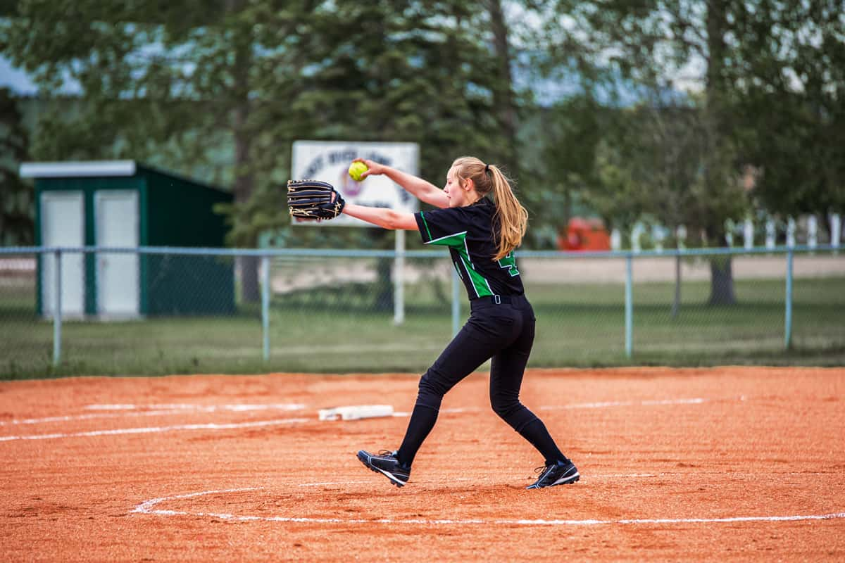 A teenage girl going to throw a softball to the batter