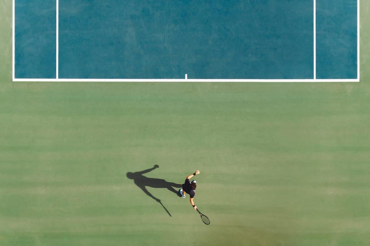 A tennis player hitting a tennis ball captured on a top view