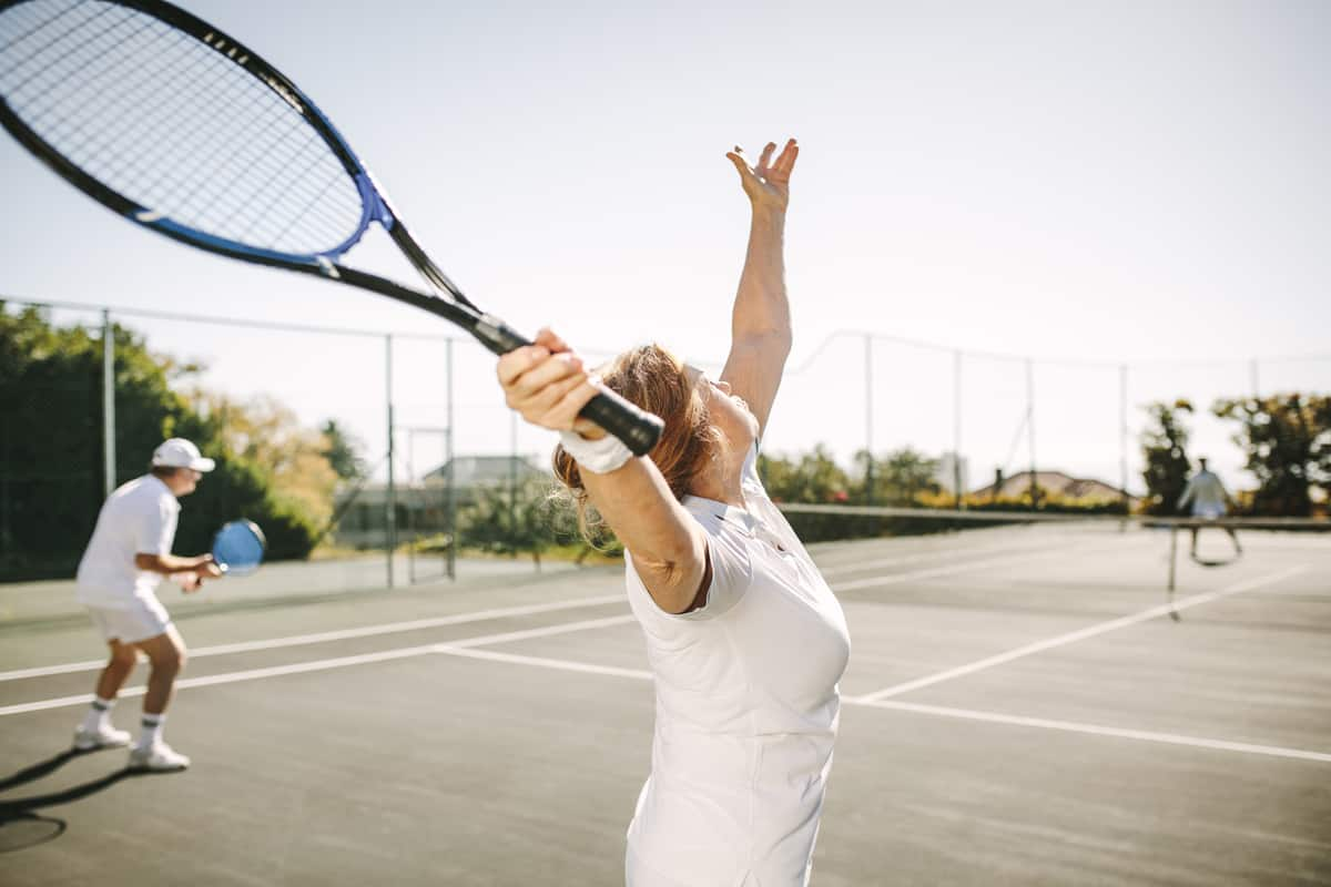 A tennis player serving the ball on a serving position to hit the ball