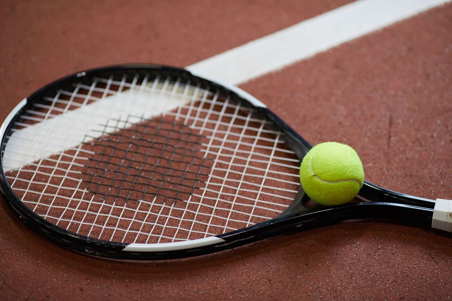 A tennis racket with a tennis ball left on the tennis court