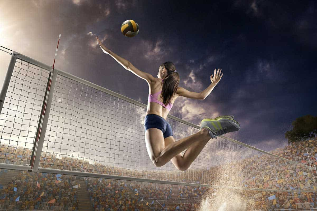 Beautiful female volleyball player performs an emotional game moment on the sand volleyball stadium with bleachers full of people, Can You Wear Basketball Shoes For Volleyball?