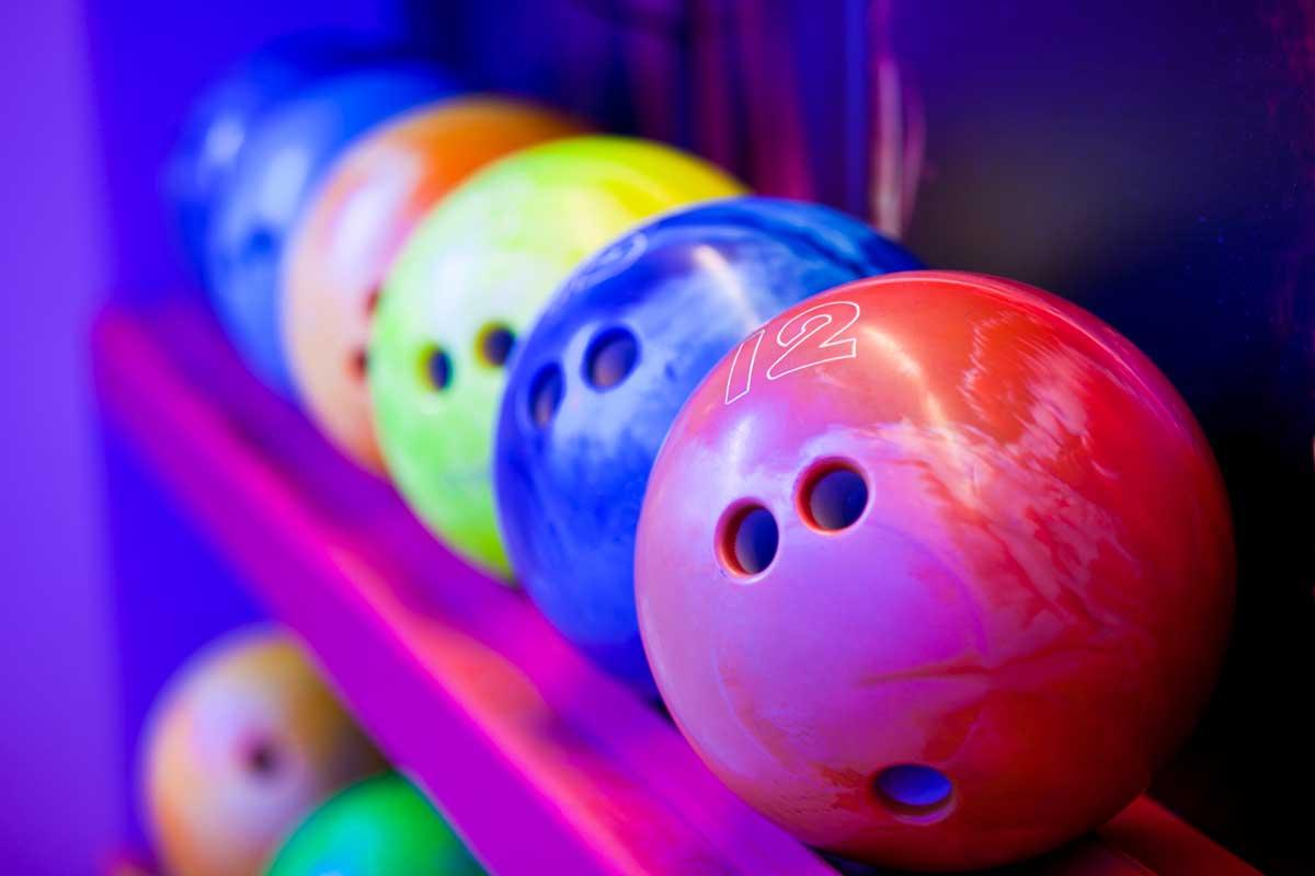 Bowling balls on ball shelves. Cosmic bowling colors