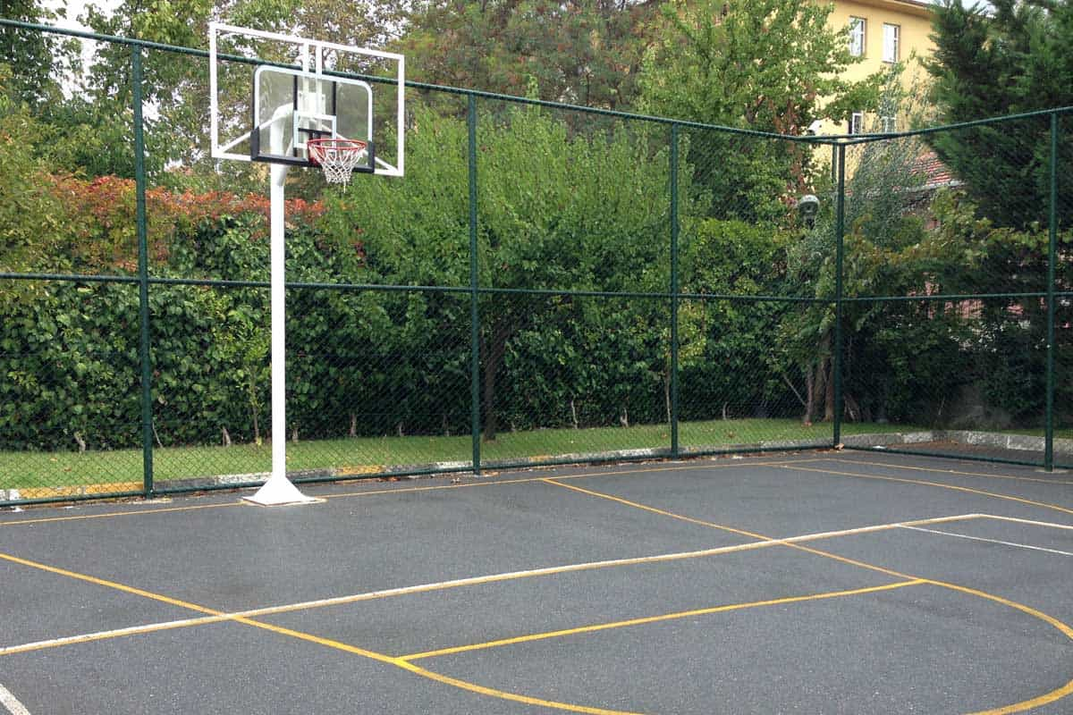 Concrete basketball court in the backyard of a home, How To Build A Concrete Basketball Court? [5 Steps]