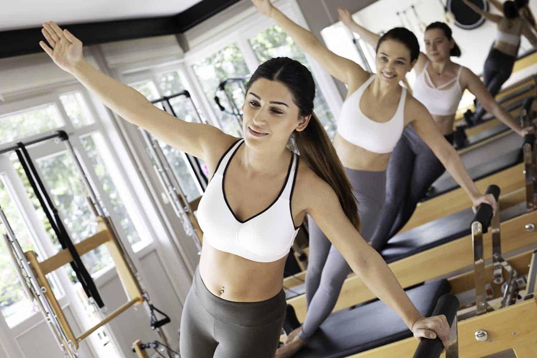 Females doing side plank on reformer in pilates studio