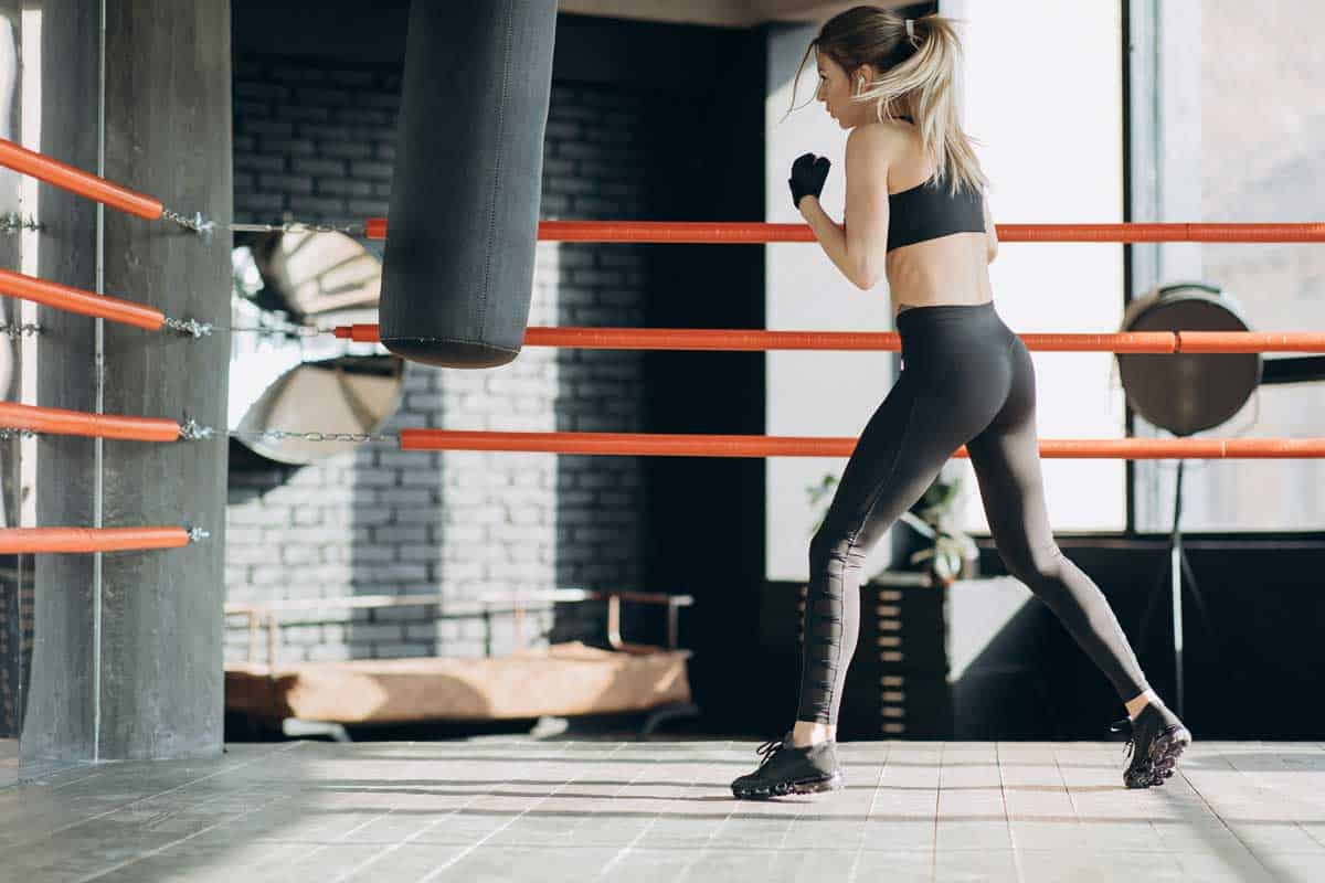 Kickboxing woman in airpods training punching bag in fitness studio fierce strength fit body