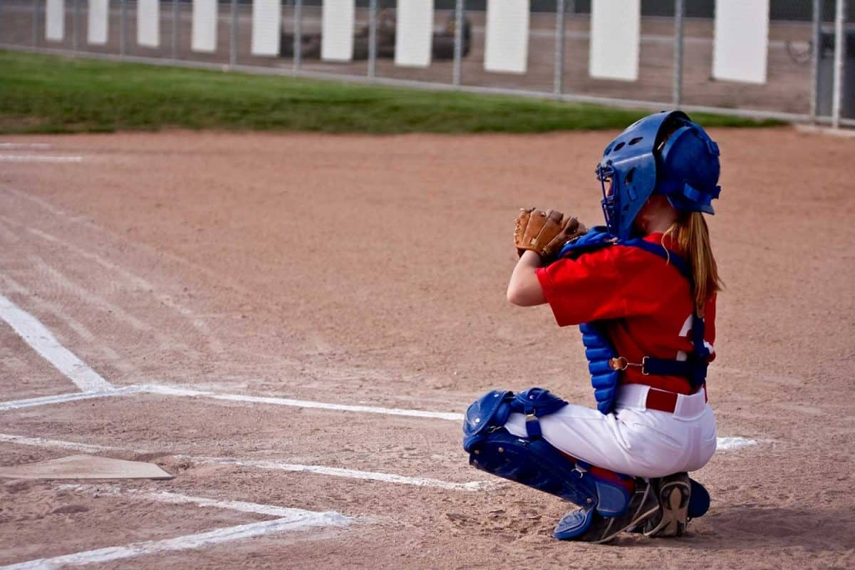 Little girl getting ready to play catcher in a softball game