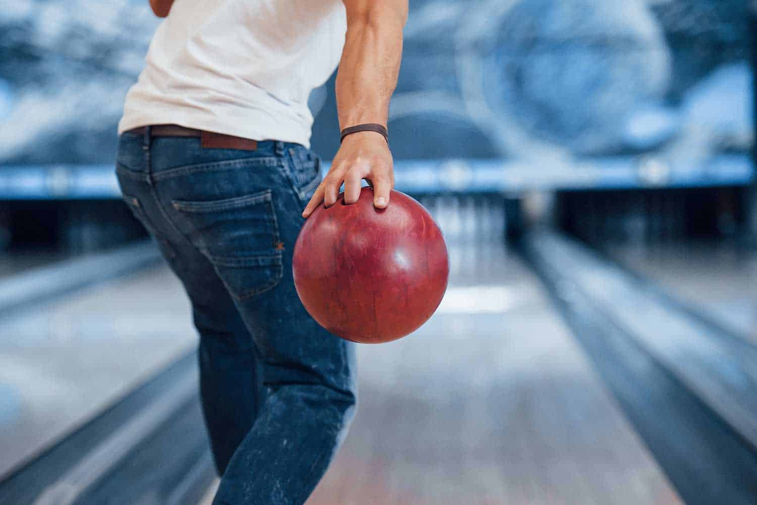 Man in casual clothes at the bowling alley playing bowling