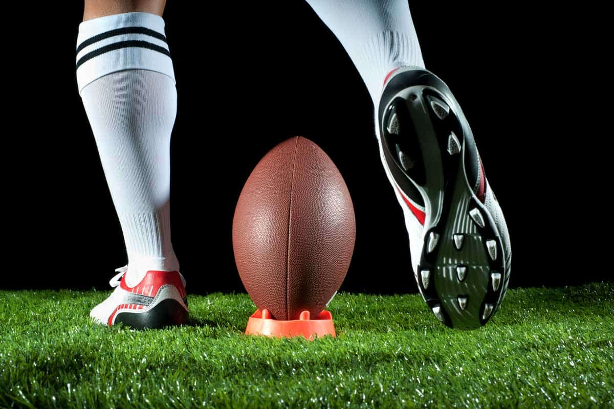 Man kicking an American football. Rear view., Can Football Cleats Be Used For Running?