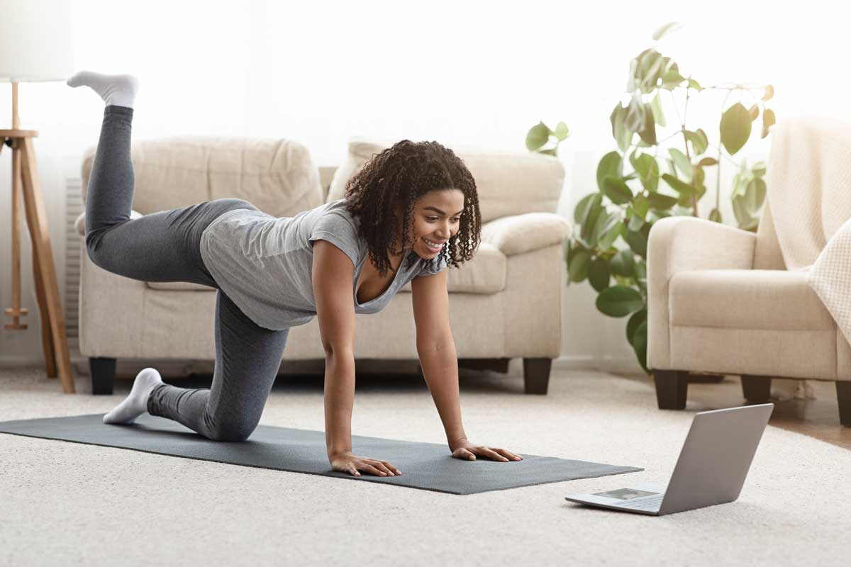 Online Training. Fit Young Woman Excercising At Home, Watching Pilates Video Tutorial On Laptop, How Much Does Pilates Cost?