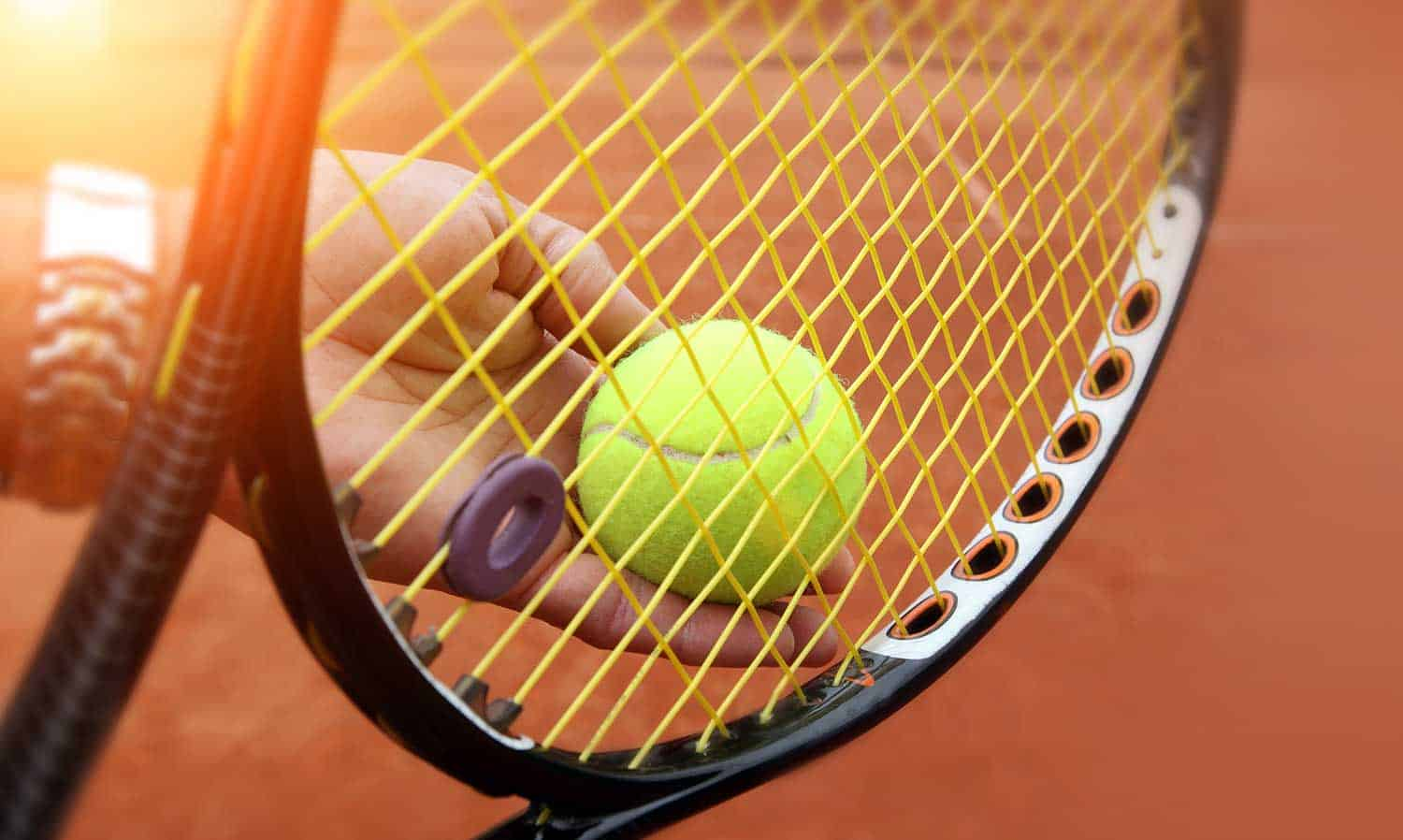 Person holding tennis racket and tennis ball getting ready to serve