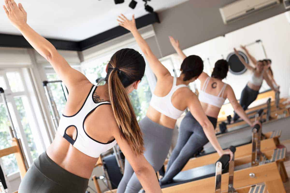 Three females doing side plank on reformer in pilates studio