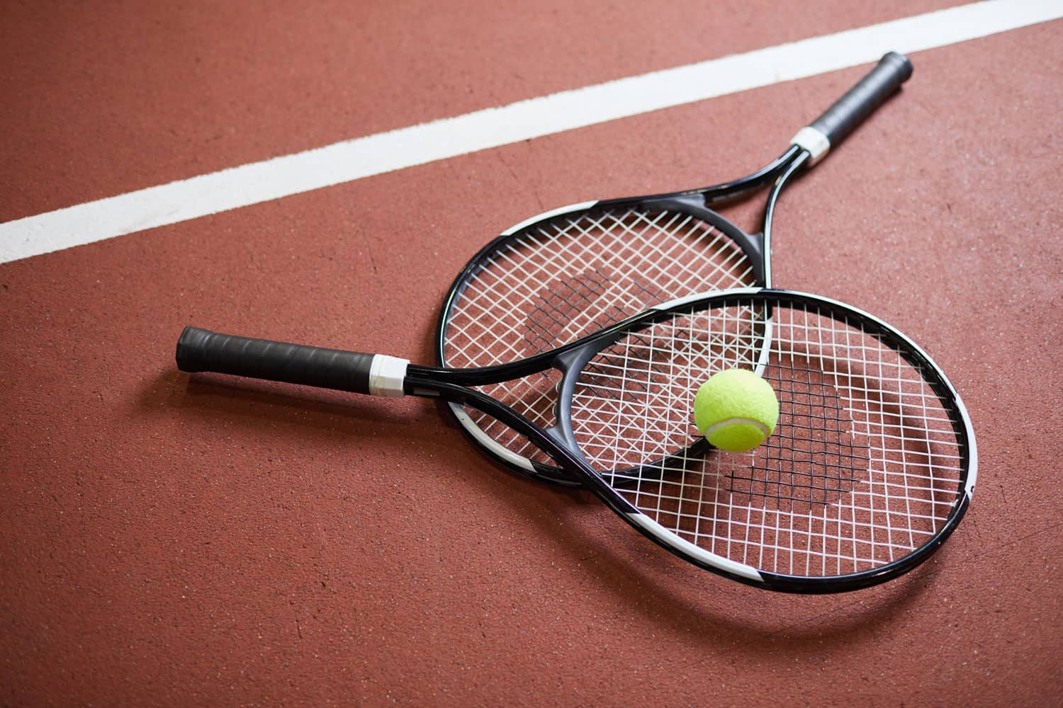 Two tennis rackets and a tennis ball placed on the side of a tennis court