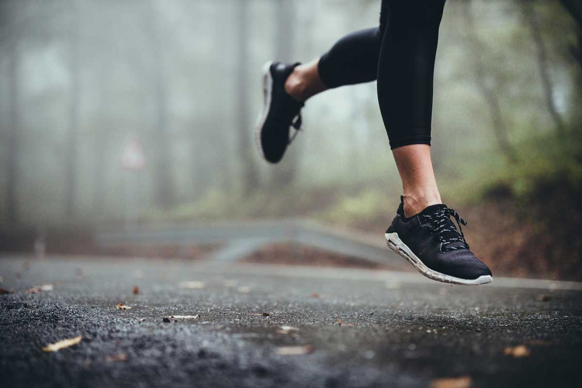 Unrecognizable athletic woman running on the road during foggy day in nature