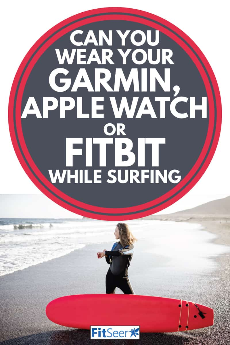 young lady surfer with surfboard on the beach checking her smartwatch, Can You Wear Your Garmin, Apple Watch Or FitBit While Surfing
