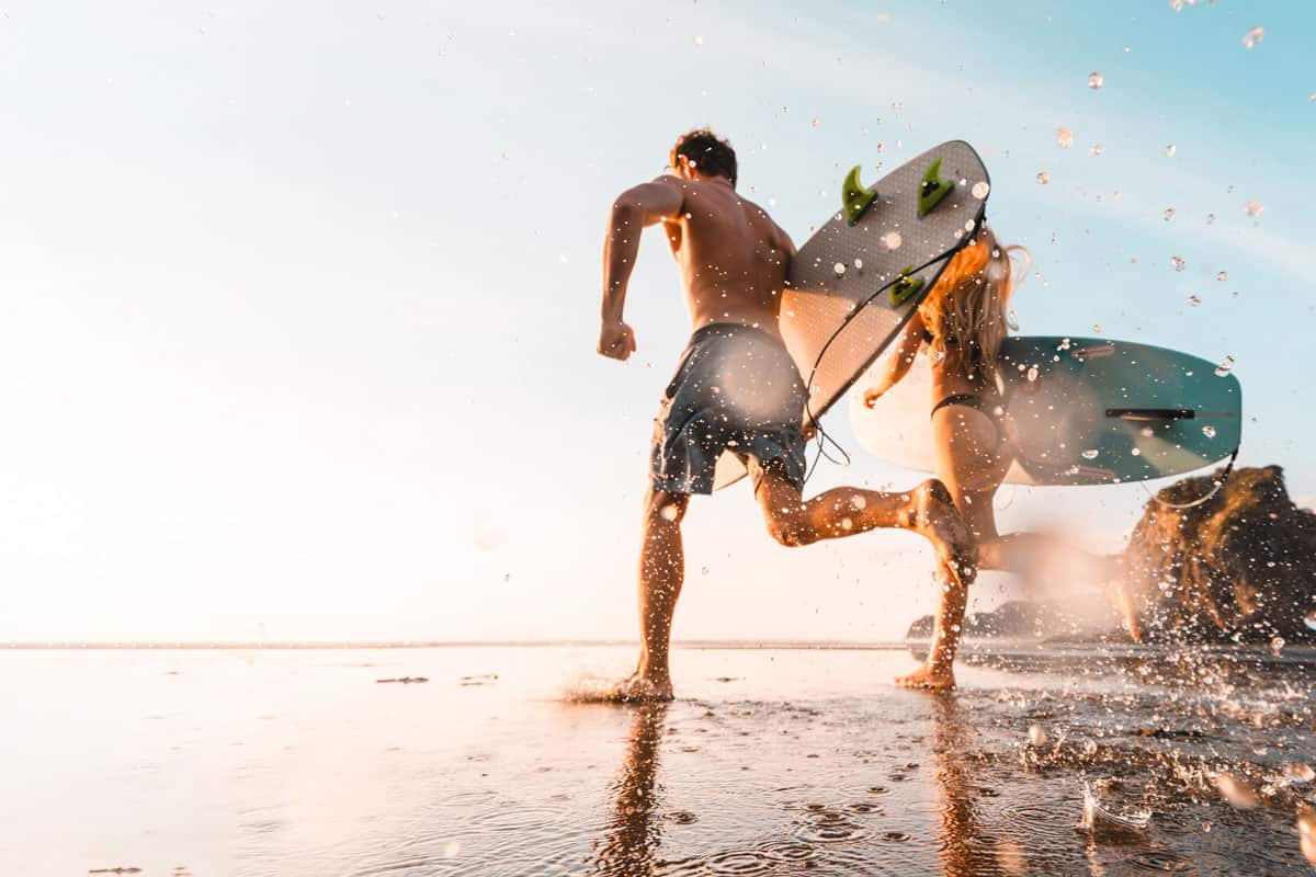 Couple holding surfboards and running towards beach for surfing