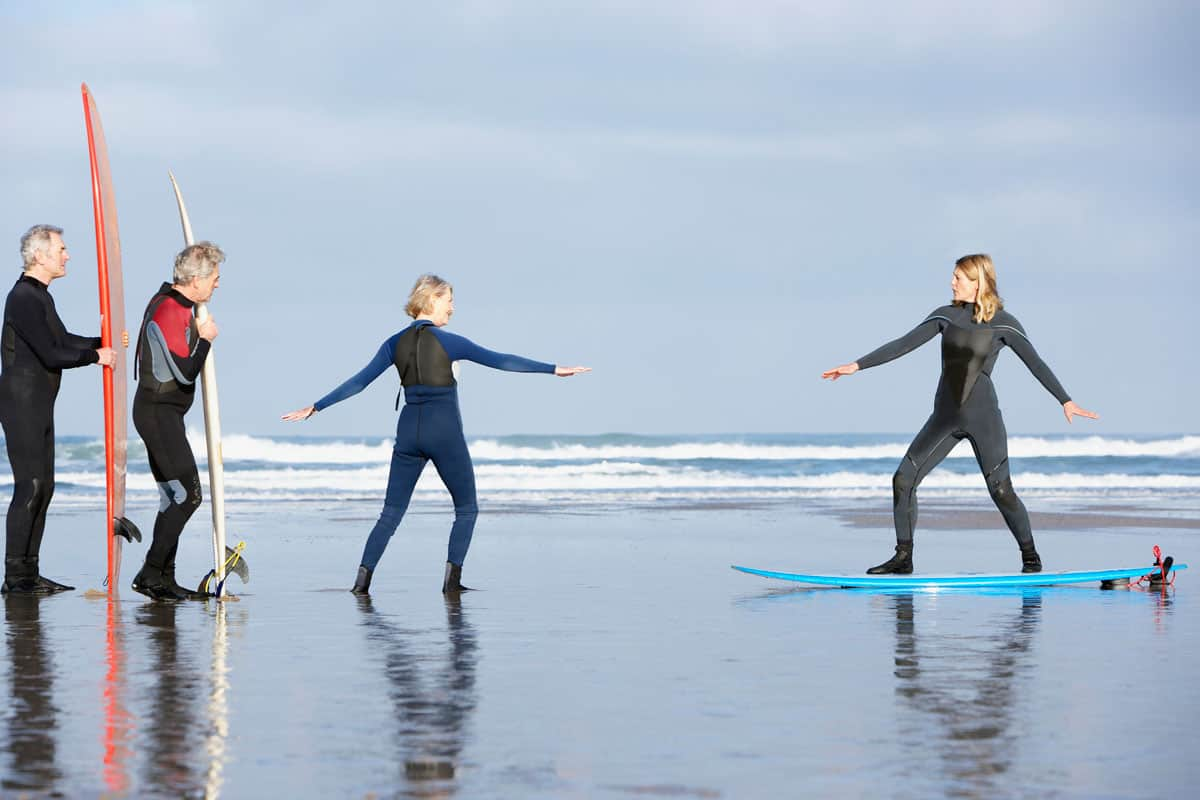 Four adults on the beach with surfboards