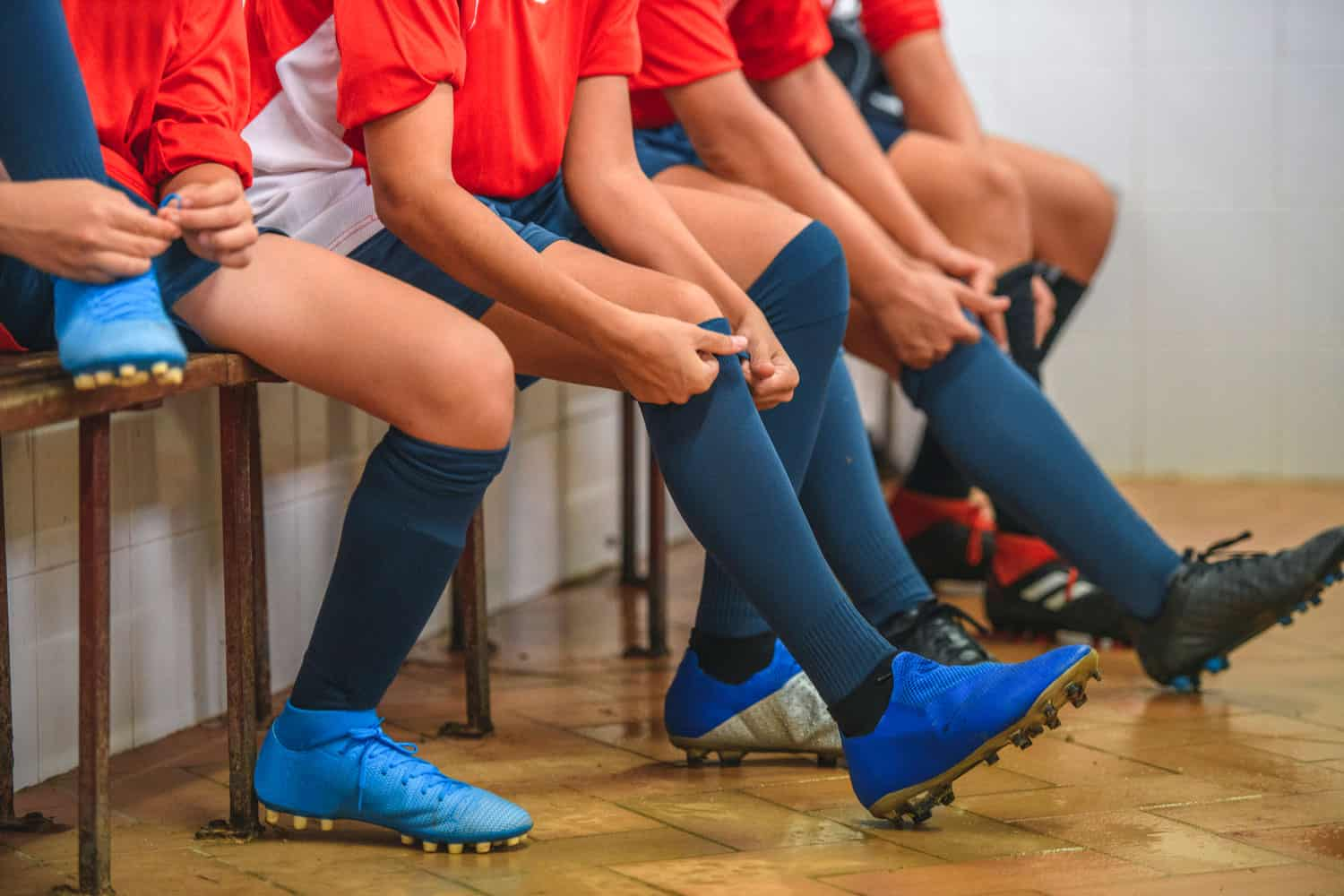 Partial view of boy footballers wearing red jerseys and putting on socks and shoes in locker room before practice, Should Football Cleats Be Tight Or Loose?