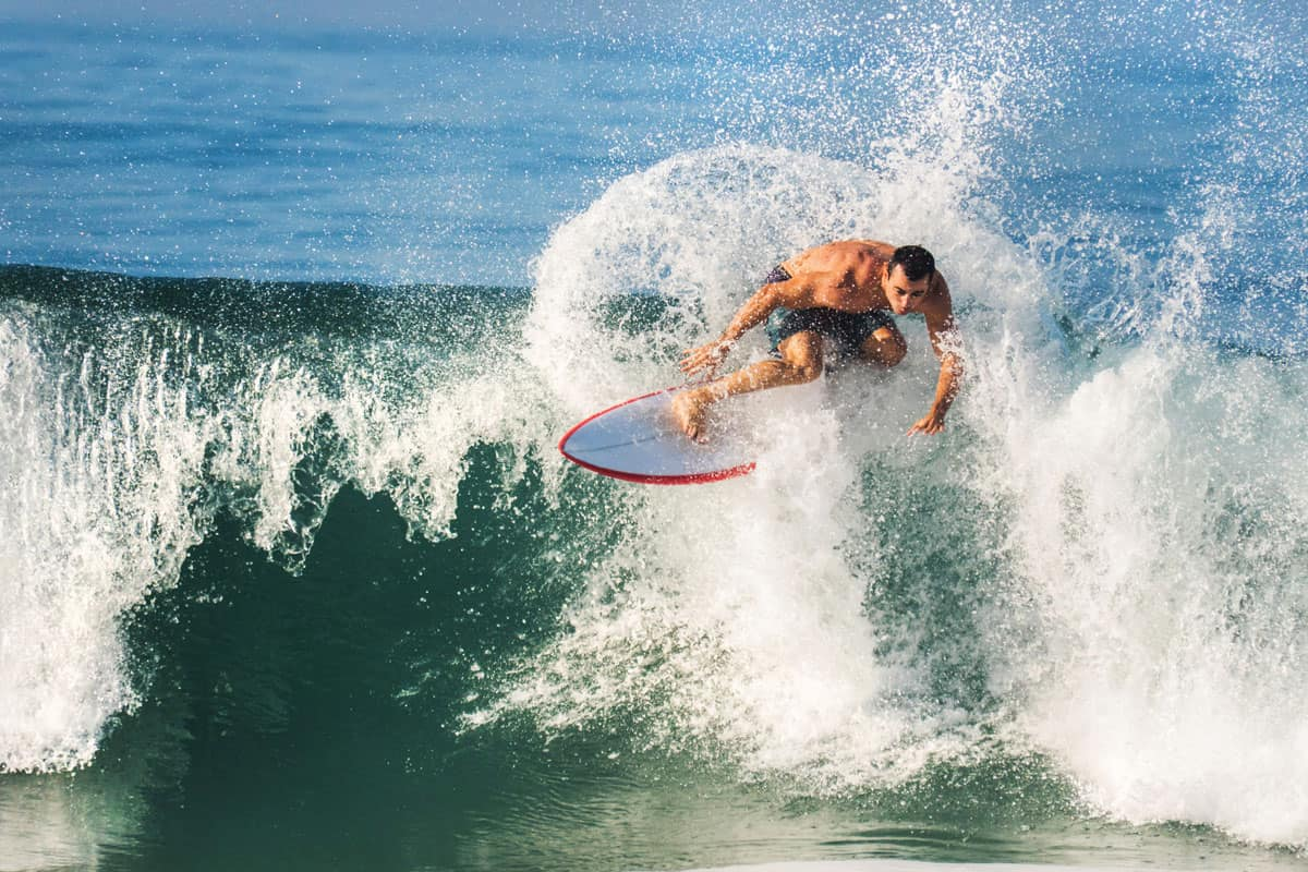 Young man surfing and trying to catch pipeline wave