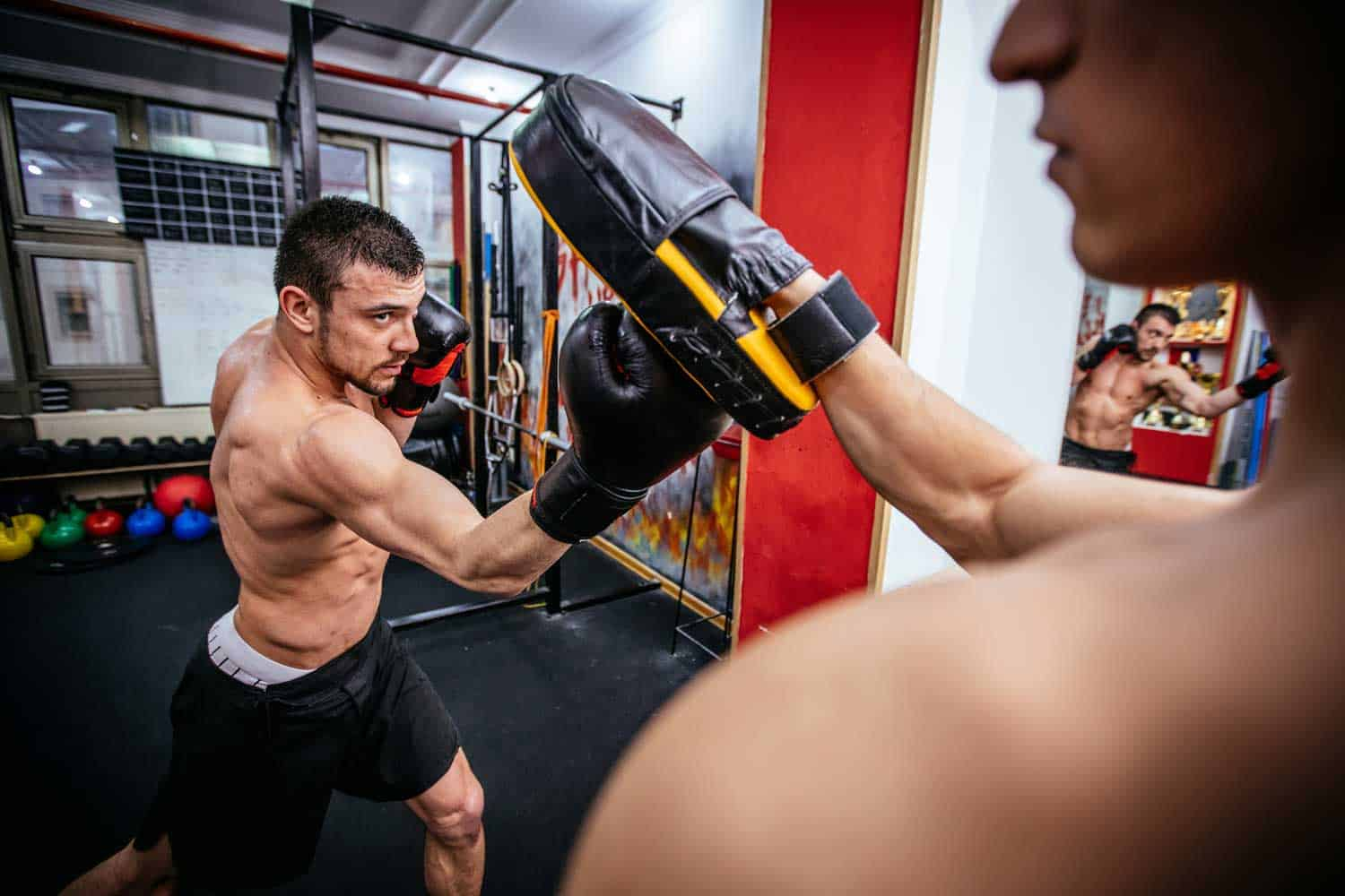 Young muscular man doing boxing exercise with trainer