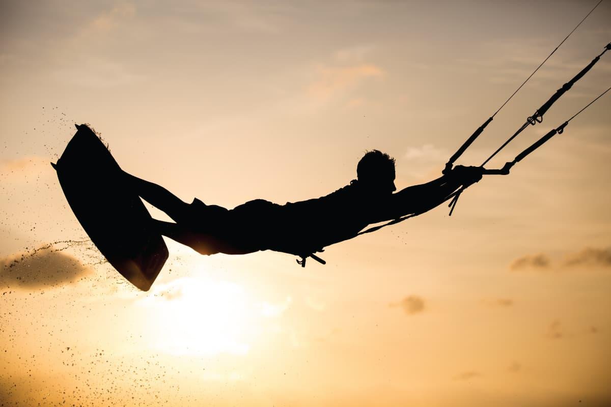 man flying while kitesurfing