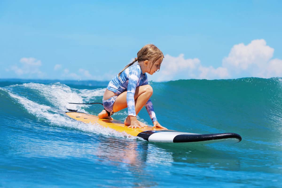Young surfer girl ride on surfboard with fun on sea waves