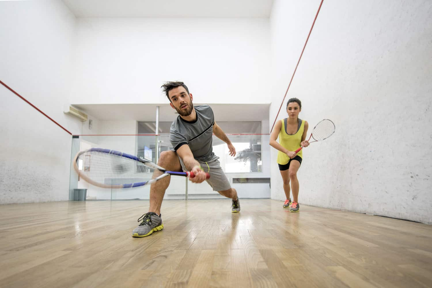 A couple playing in a squash court