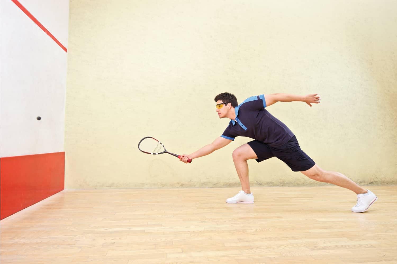 A squash player hitting a ball in a squash court
