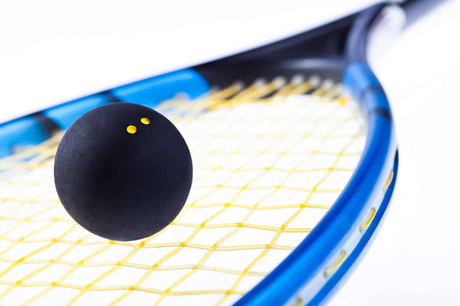 An up close photo of a squash ball hitting the racket