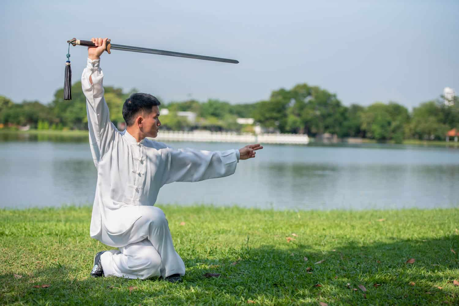 Asian man practicing with Tai Chi sword in the morning at the park
