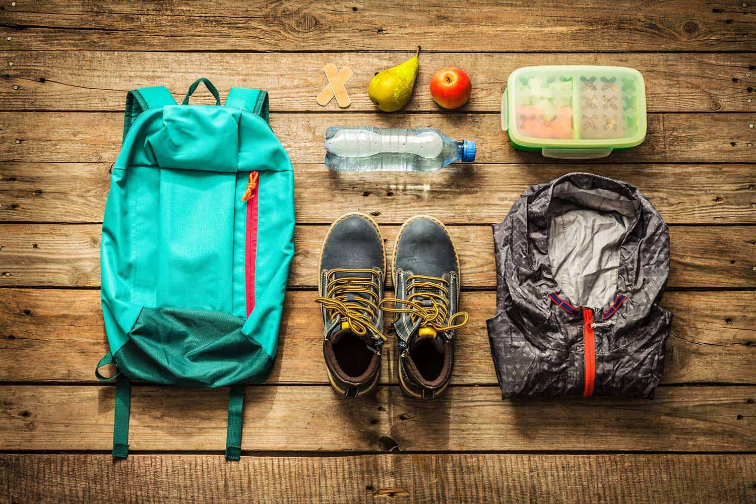 Backpack, boots, jacket, lunch box, water and fruits on wooden background