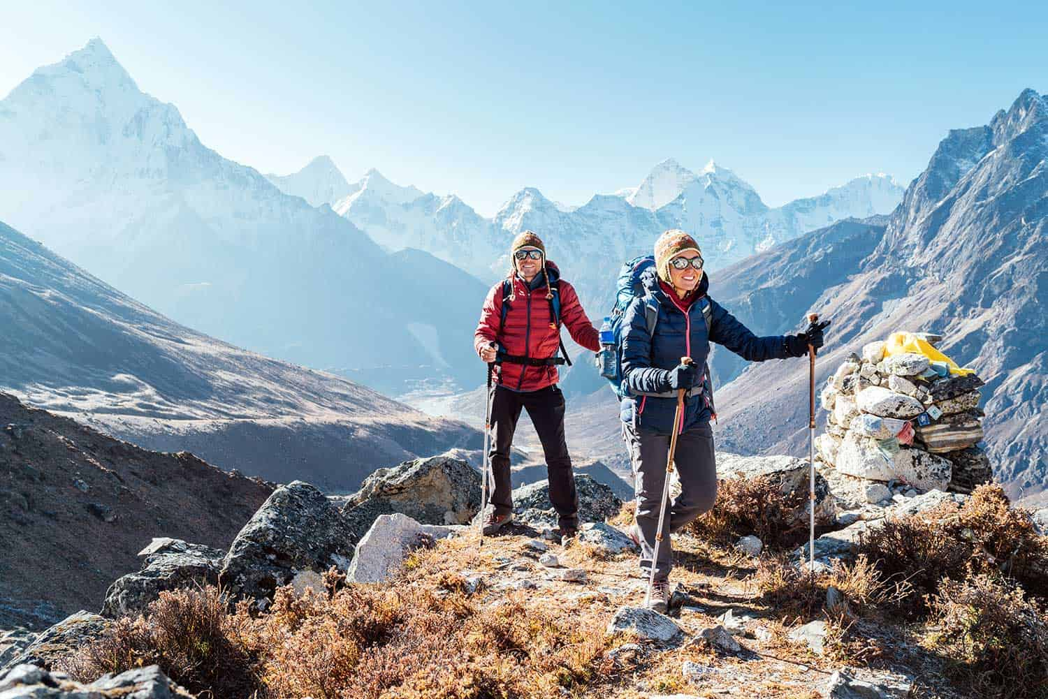 Backpackers carrying backpacks, using trekking poles and enjoying valley view