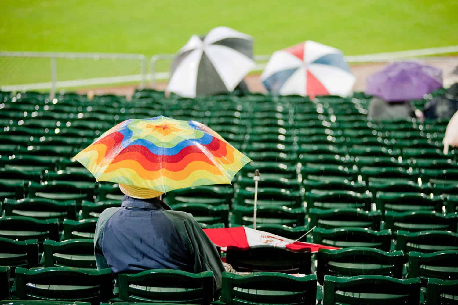 Baseball spectators using umbrellas while watching the game