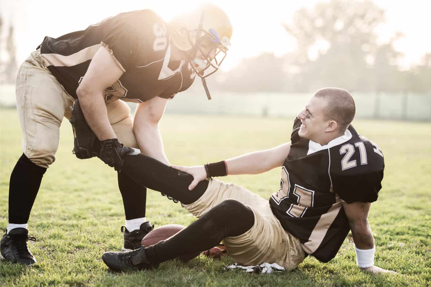 Injured American football player sitting on a grass while his friend is helping him