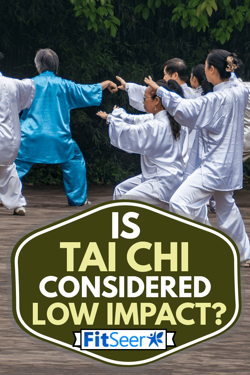 Group of people in silver and blue silk outfits practicing synchronized Tai Chi exercises in front of green foliage wall, Is Tai Chi Considered Low Impact?