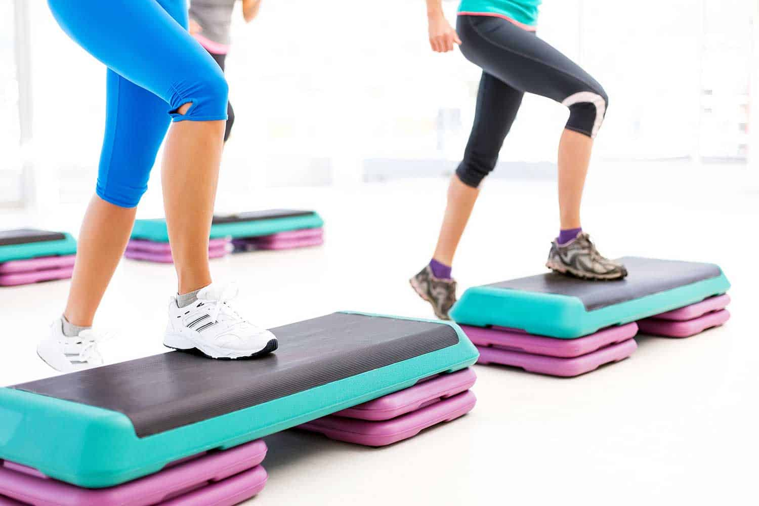 Low section of female friends doing step aerobics in health club