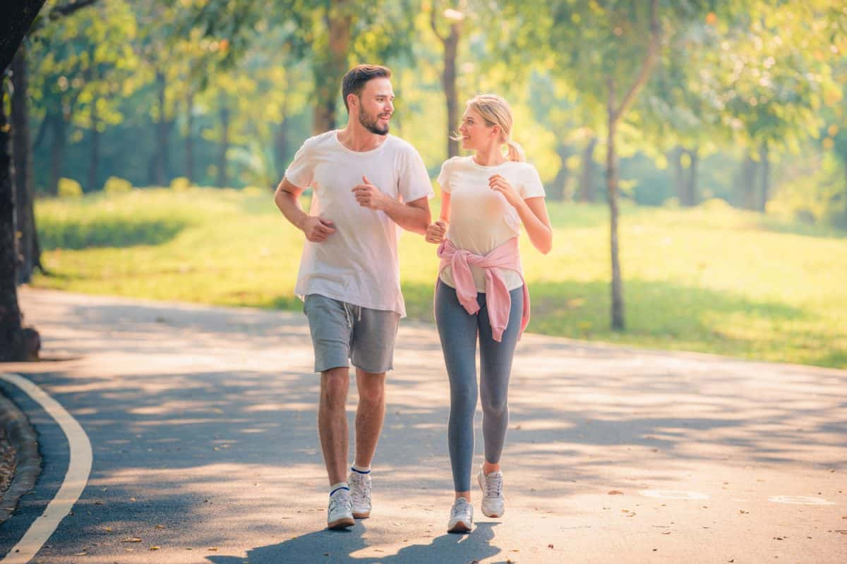 Portrait of Young couple running in the park at sunset, Does Walking Make Your Legs Bigger or Thicker?