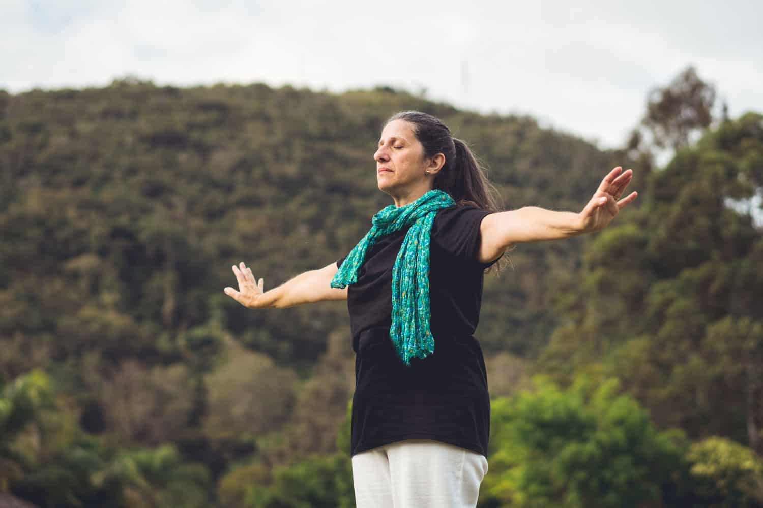 Woman meditating with arms raised