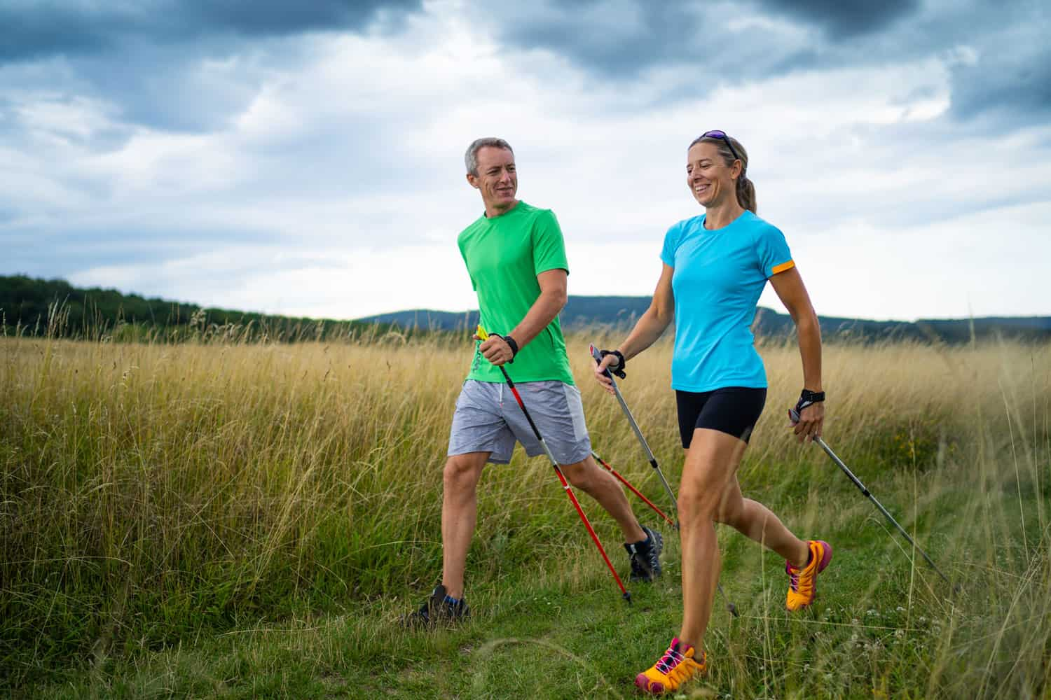 active smiling middle aged couple doing nordic walking sport in grassland with shallow focus cloudy overcast sky dark clouds front view, Does Walking Make Your Legs Bigger or Thicker?