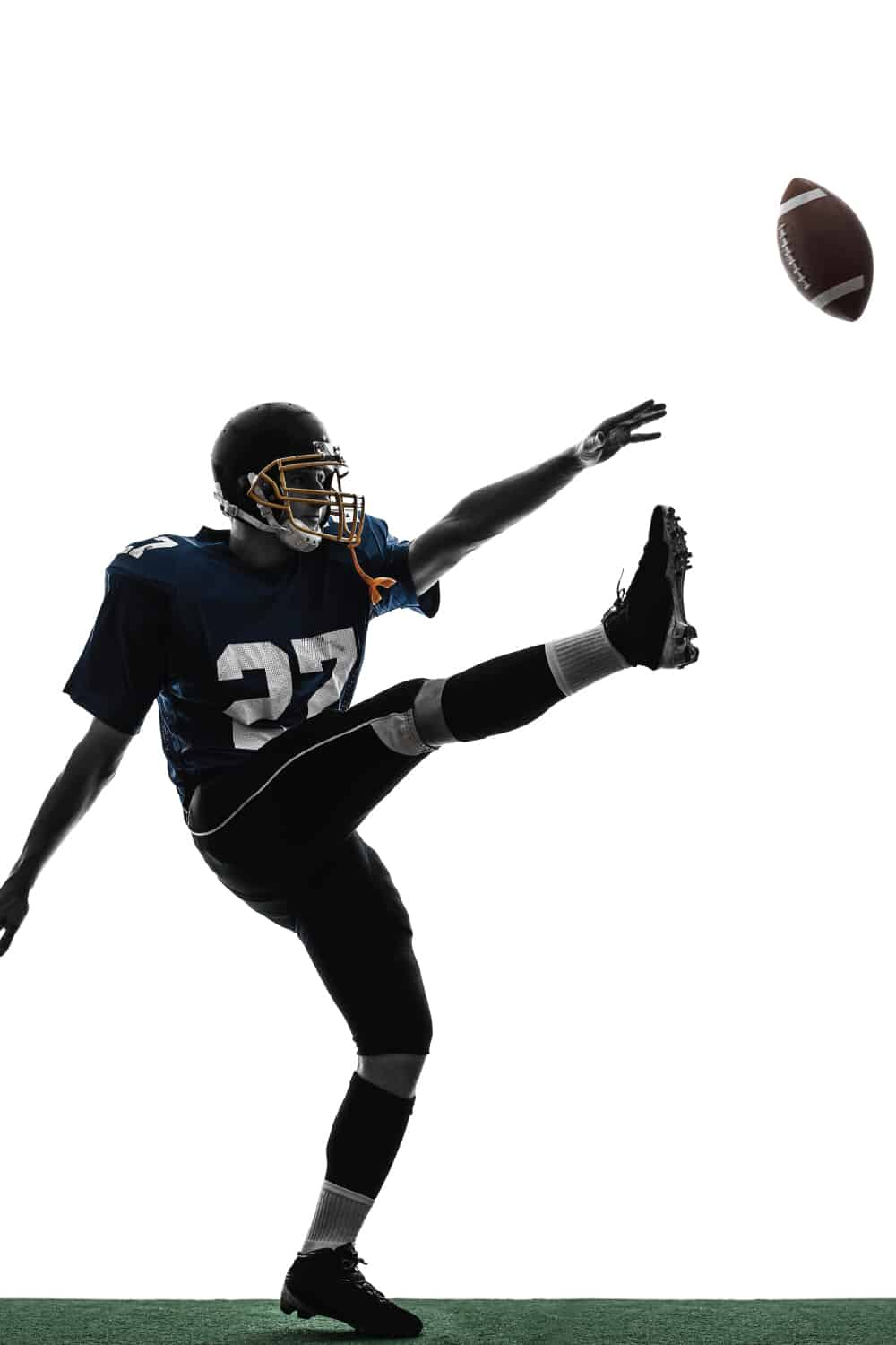 American football player kicking the ball in silhouette