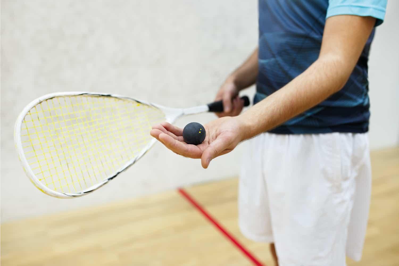 A man holding a squash ball preparing to serve