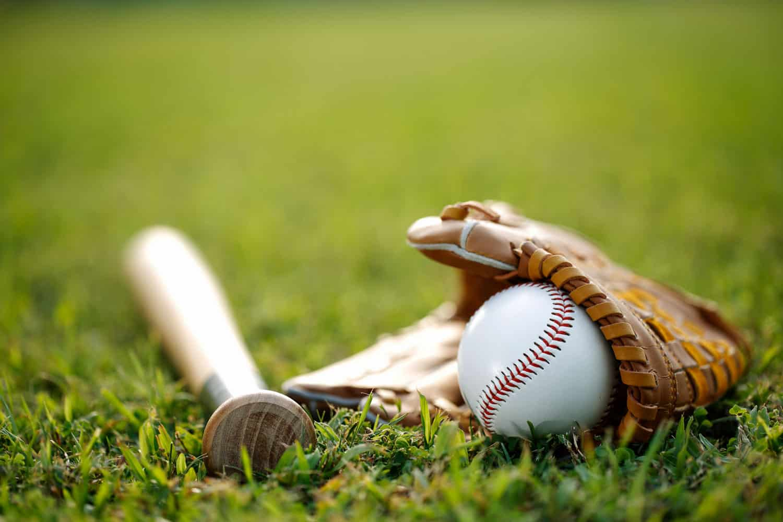 A baseball bat glove and ball on a baseball field