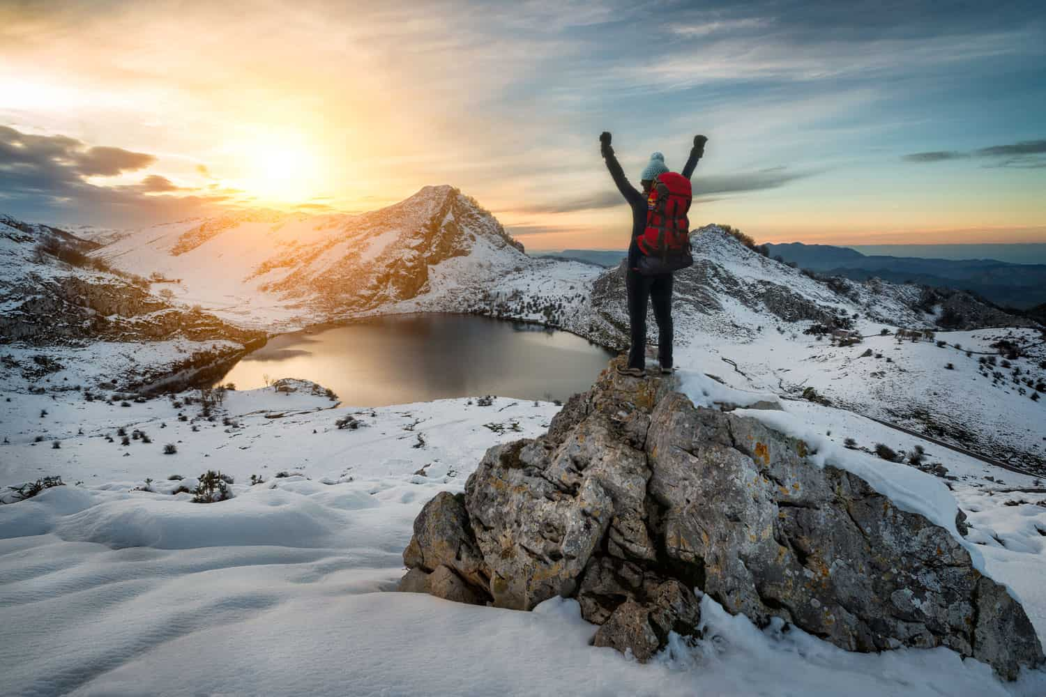 A man raising his arms after reaching the summit of a snow mountain